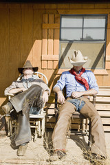 Two cowboys sleeping in chairs