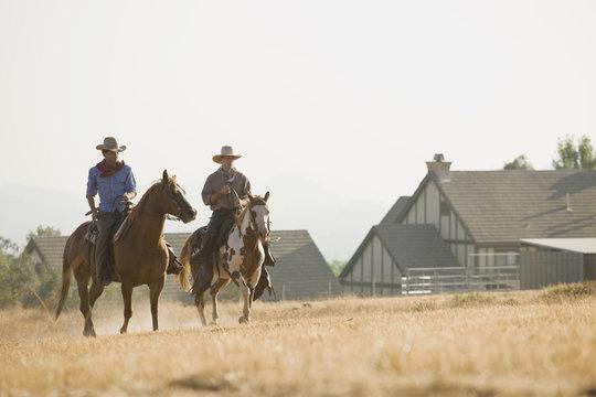 Two cowboys riding horses through a field