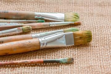 artist brush lying on sackcloth, Paint brushes and palette knife