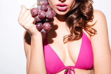 Cropped image of a girl holding grapes wearing bikini