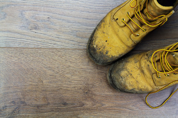Muddy work boots on a wooden floor