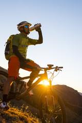 Biker drinking and enjoying the evening sun