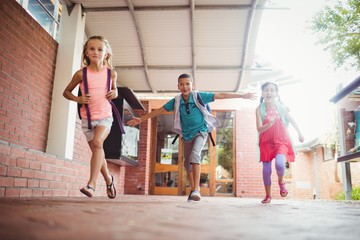 Three kids running in the playground
