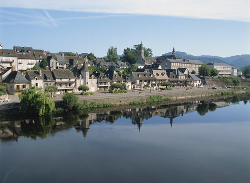 Reflections in the River Dordogne of houses and churches of Argentat in Correze, Limousin, France
