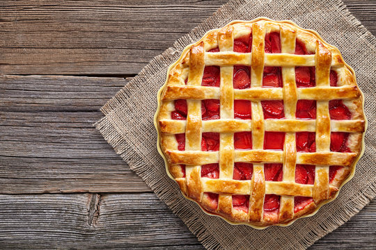 Traditional gourmet strawberry pie tart cake sweet baked pastry food on rustic wooden table background