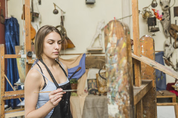 Female painter holding paintbrush and looking at easel at studio