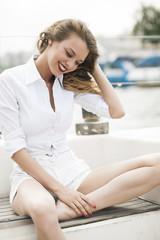 красивая девушка в белой рубашке на палубе яхты
