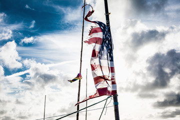 Tattered American flag on pole against cloudy sky