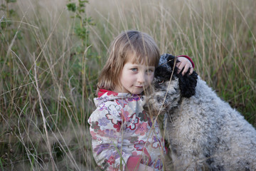 Portrait of cute girl sitting with dog on field