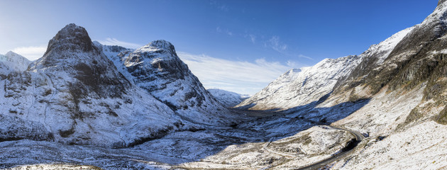 Winter view down snow-covered Glencoe showing Three Sisters of Glencoe and the A83 winding through the glen towards Glencoe Village, Highland, Scotland, United Kingdom, Europe