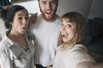 Portrait of young man with female friends having fun at home