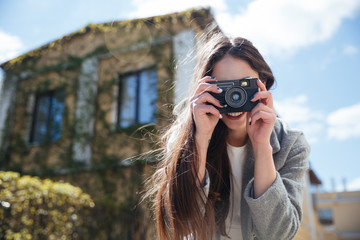 Young smiling brunette taking picture with photo camera outdoors