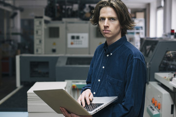 Portrait of confident young male technician using laptop in factory