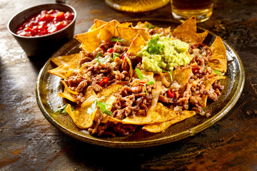 Cheese nachos with beef, guacamole and salsa