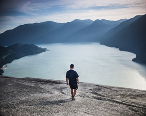 Full length rear view of man walking towards river against Stawamus Chief Mountain
