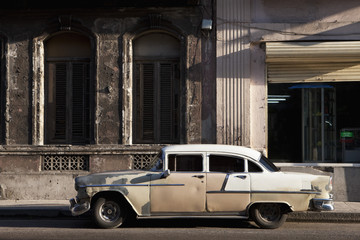 Old vintage car parked on street outside building