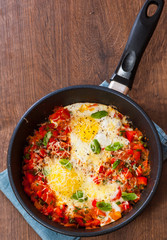 fried eggs with vegetables and cheese in a frying pan on wooden table