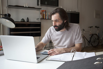 Mid adult man working on laptop at home
