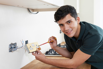 Portrait Of Electrician Installing Socket In New House