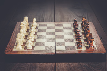 chess board with figures on the wooden table background