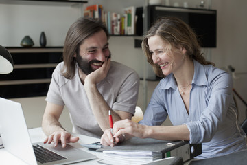 Happy couple using laptop while working from home