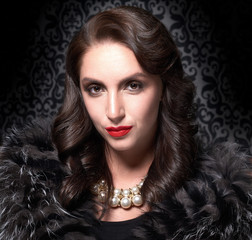 Portrait of elegant brunette retro woman wearing silver fox fur over vintage background