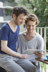 Gay couple using digital tablet at porch