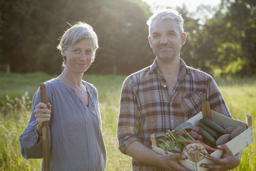 Portrait of mature couple with crate of freshly harvested vegetables