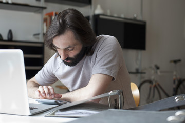 Mid adult man using calculator at table