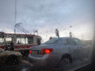 blurred view of road traffic through the car window with drops.