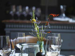 Close-up of flower vase and wine glasses in the restaurant