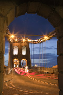 View along the A5 road at night across the Menai suspension bridge, built by Thomas Telford in 1825, Bangor, Gwynedd, North Wales.