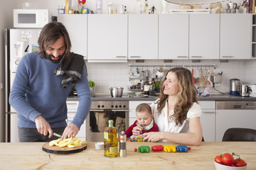 Father chopping vegetables with wife and daughter sitting in kitchen Fototapete