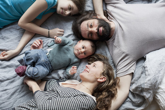 Overhead view of family relaxing on bed