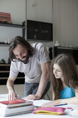 Smiling father assisting daughter in doing homework at table