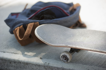 Close-up of skateboard and bag on sidewalk