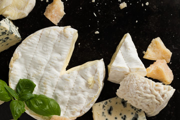 Cheese assorted on a table background. Variety sorts for appetizing, gourmet, delicious snacks. Traditional French dish for wine on lunch and dinner closeup. Camembert, Roquefort.
