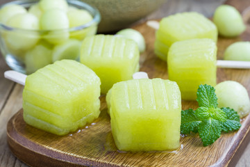 Homemade melon popsicles on a wooden background