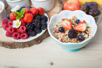 Paleo style breakfast: gluten free grain free oat free granola with mixed nuts, and fresh berries and fruits, selective focus