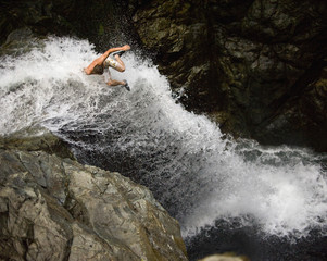 Man jumping in to waterfall, Lynn Canyon, Vancouver, Canada