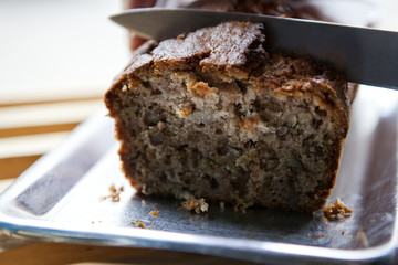 A knife cutting into a loaf of banana bread in a cafe