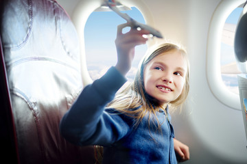 Adorable little girl traveling by an airplane. Child sitting by the window and playing with toy plane.