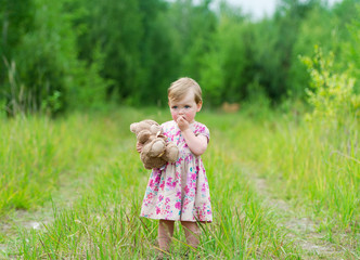 Little girl standing in grass holding large teddy bear.