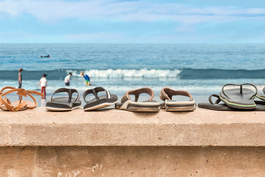 Sandals lined up on a stone wall ledge at the beach, blurry people background