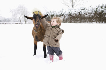 Baby girl putting her hat on goat
