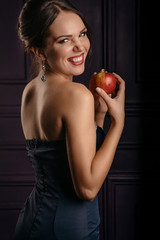 beautiful young woman in a blue dress holding an apple