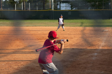 Boy preparing to swing a bat on baseball pitch