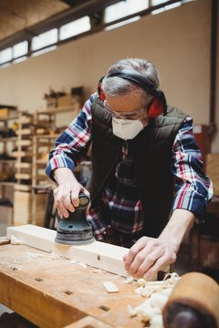 Carpenter sanding down a plank of wood