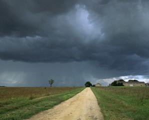 Straight rural dirt road through farmland near Le Mans, overcast stormy sky, Sarthe in Loire, Centre, France, Europe