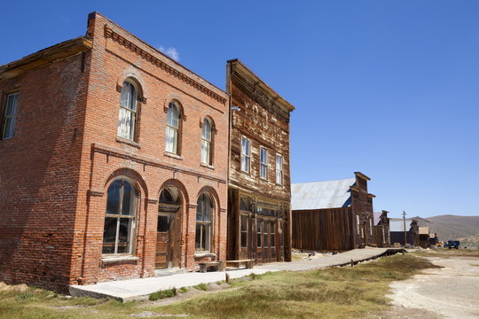 Brick Post Office and Dechambeau hotel, next to the wooden IOOF or Bodie Odd Fellows Lodge, a masonic lodge dating from 1878, on Main Street in the gold mining ghost town of Bodie, Bodie State Historic Park, Bridgeport, California, United States of Americ